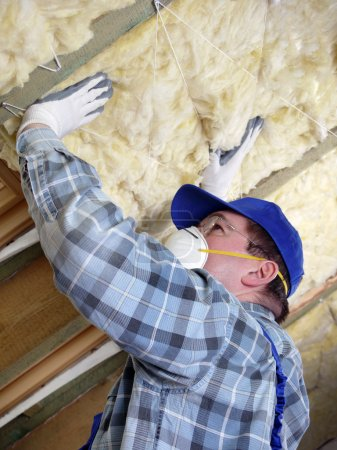 Foto de Trabajador que aísla térmicamente un ático de la casa usando lana mineral - Imagen libre de derechos