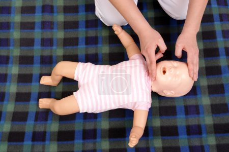 Photo for Infant dummy first aid demonstration series - First aid instructor showing how to position infant head before proceeding to mouth-to-mouth resuscitation - view from above - Royalty Free Image