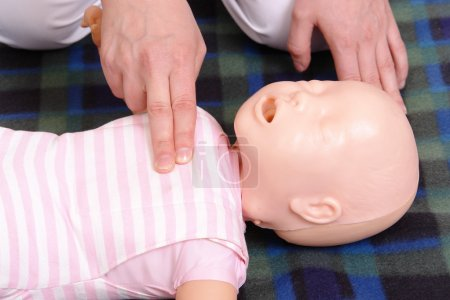 Photo for Infant dummy first aid demonstration series - first aid instructor demonstrating how to check infant life functions - Royalty Free Image