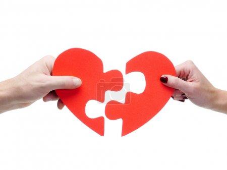 Foto de Macho y hembra que empareja las mitades de corazón rompecabezas rojo sobre fondo blanco de la mano - Imagen libre de derechos