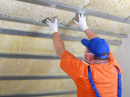 Foto de Trabajador de la construcción aislante térmicamente ático casa con lana mineral - Imagen libre de derechos