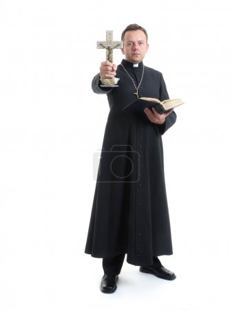 Catholic priest holding Holy Cross and Bible perfo...