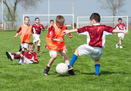 Photo for Children playing soccer on the sports field - Royalty Free Image