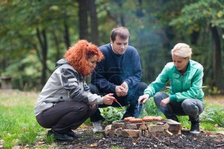 Photo pour Amis faire un barbecue dans les bois - image libre de droit