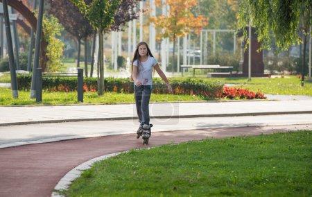 Girl rides on roller skates...