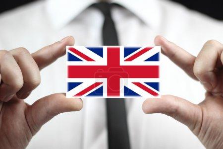 Photo pour Homme d'affaires détenant une carte de visite avec un drapeau uk - image libre de droit