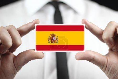 Photo pour Homme d'affaires titulaire d'une carte de visite avec drapeau espagnol - image libre de droit