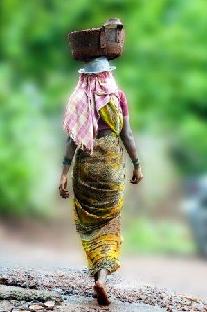 Photo pour Managlore, Inde - 12 juin : Une travailleuse de la construction inconnue en Inde, qui s'acquitte de sa tâche habituelle de transporter des matériaux sur la tête. Une pratique courante sur tout chantier non aménagé . - image libre de droit