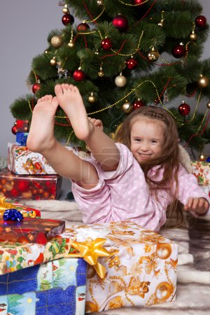 The girl with a gift under the Christmas tree