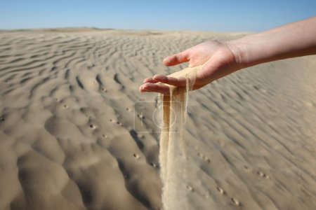 Sand slipping through the fingers of a woman's hand in the desert of Sahara in Tunisia.