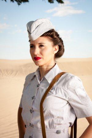 Photo pour Une belle jeune infirmière de la Seconde Guerre mondiale, en uniforme authentique, regarde au loin dans le paysage poussiéreux sec. fermer la tête et les épaules. Uniforme est le seersucker gris à rayures avec casquette sans visière portée par les infirmières de la marine américaine . - image libre de droit