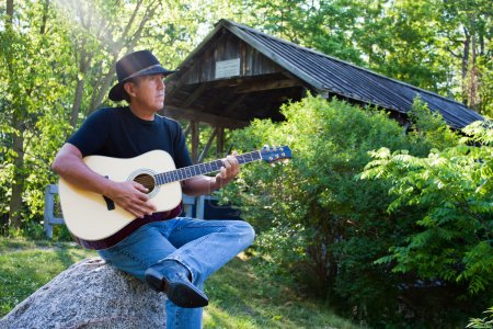 Country Guitar player at covered bridge