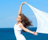 fille avec une écharpe blanche sur la plage. voyages et vacances