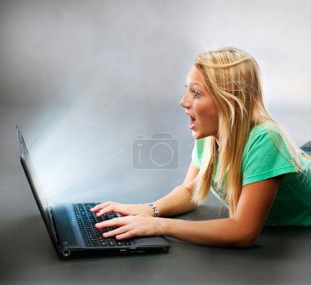 Photo pour Surprise fille avec un ordinateur portable. Travailler sur ordinateur - image libre de droit