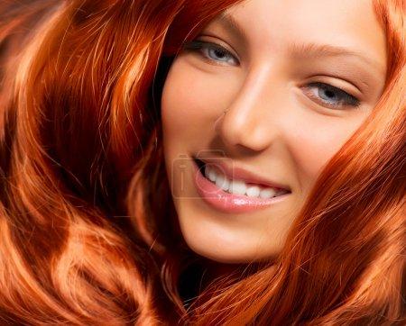 Cabello. Hermosa chica con cabello largo y rizado rojo saludable