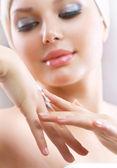 Crème mains. femelle en appliquant la crème hydratante à la main après le bain