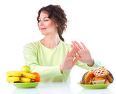 Diet. Beautiful Young Woman choosing between Fruits and Sweets