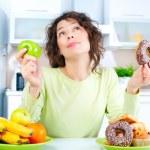 Diet. Beautiful Young Woman choosing between Fruit...