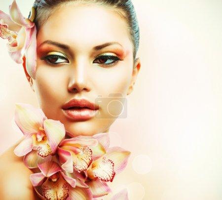 Foto de Hermosa chica con orquídeas flores. cara de una mujer de belleza - Imagen libre de derechos