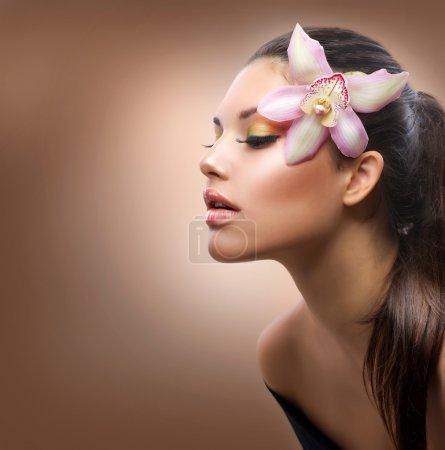 Foto de Retrato de belleza. hermosa chica con estilo con orquídeas Phalaenopsis - Imagen libre de derechos