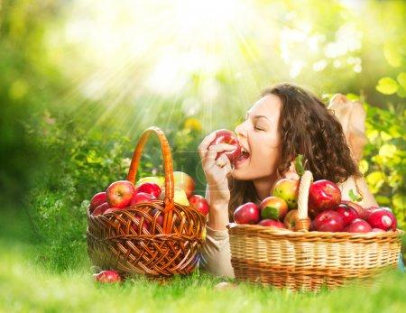 Beautiful Girl Eating Organic Apple in the Orchard