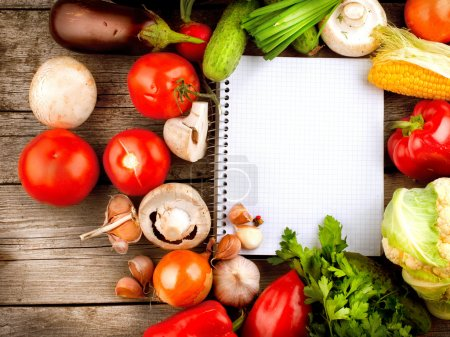 Photo for Open Notebook and Fresh Vegetables Background. Diet - Royalty Free Image