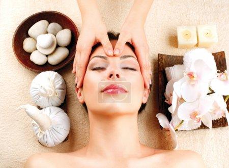 Photo pour Massage spa. jeune femme se massage facial - image libre de droit