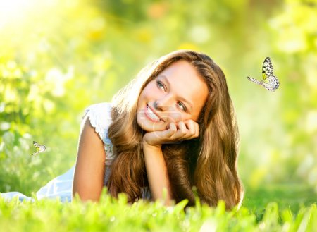 Photo for Spring Beauty. Beautiful Girl Lying on Green Grass outdoor - Royalty Free Image