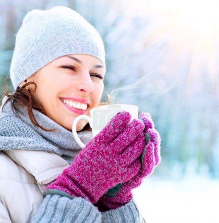 Photo pour Belle femme d'hiver souriante heureuse avec tasse extérieure - image libre de droit