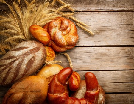 Photo for Bakery Bread and Sheaf over Wood Background - Royalty Free Image
