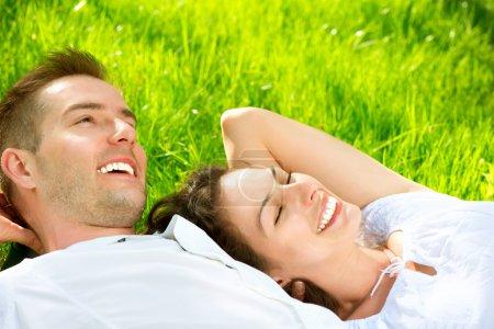 Photo pour Jeune couple couché sur l'herbe en plein air - image libre de droit