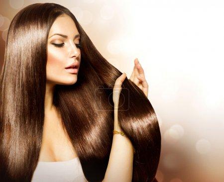 Foto de Mujer de belleza tocando su cabello castaño largo y saludable - Imagen libre de derechos