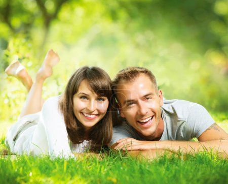 Photo for Happy Smiling Couple Together Relaxing on Green Grass Outdoor - Royalty Free Image