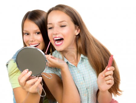 Pretty Teenage Girls Applying Make up and Looking in the Mirror