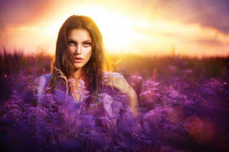 Photo pour Beauté fille couché sur une prairie avec des fleurs violettes - image libre de droit