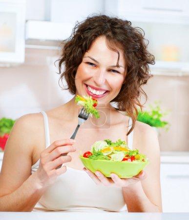 Foto de Hermosa joven comiendo ensalada de vegetal. concepto de dieta - Imagen libre de derechos