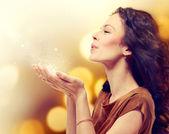Mladá žena fouká kouzelný prach s hvězdami z jejích rukou