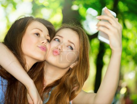 Teen friends taking photos with a smartphone.