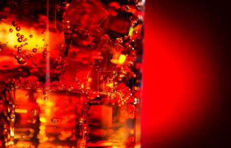 Cola with ice and bubbles in glass