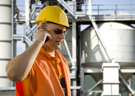 Worker with helmet and sunglasses talking on mobile phone in front of oil plant