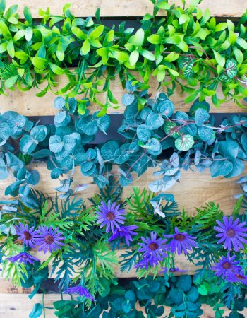 Plaastic flowers and plants in wooden pot as vertical garden.