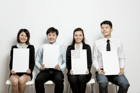 Chinese Business team hold up blank cards.