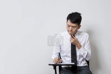 Photo pour Chinois mâle étudiant ou homme d'affaires prenant un test d'examen - image libre de droit