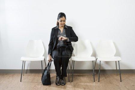 Photo pour Femme d'affaires indienne en attente pour un entretien d'embauche et de regarder l'heure. - image libre de droit