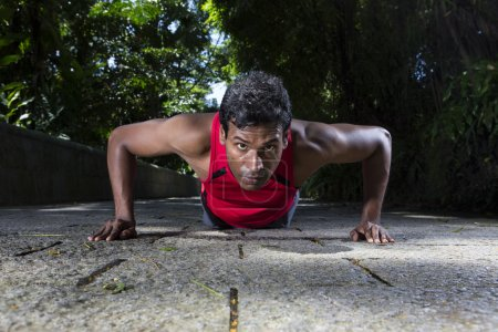 Indian man performing push up in the city park.