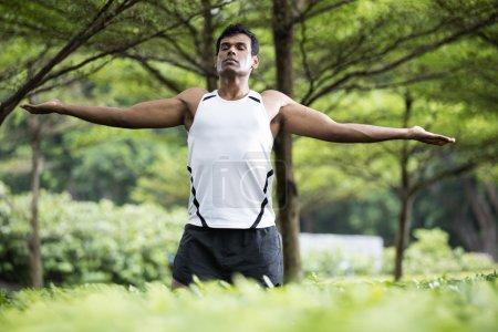 Indian man doing yoga exercise in park