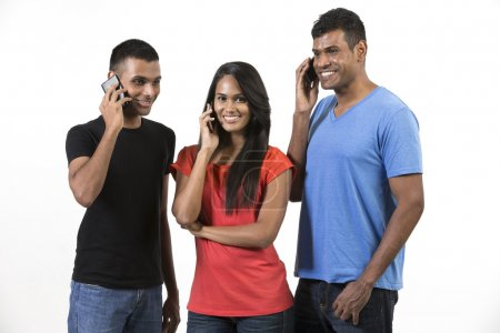 Group of young Indian friends using their smartpho...