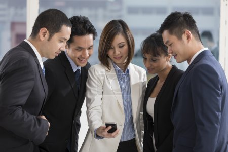 A group of business people looking at a smartphone