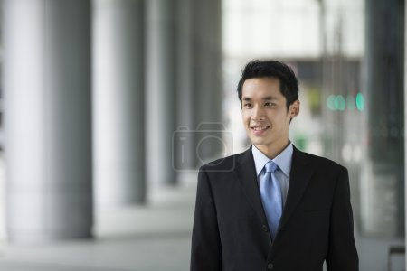 happy young Chinese business man in modern city