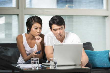 Young Chinese couple using a laptop at home